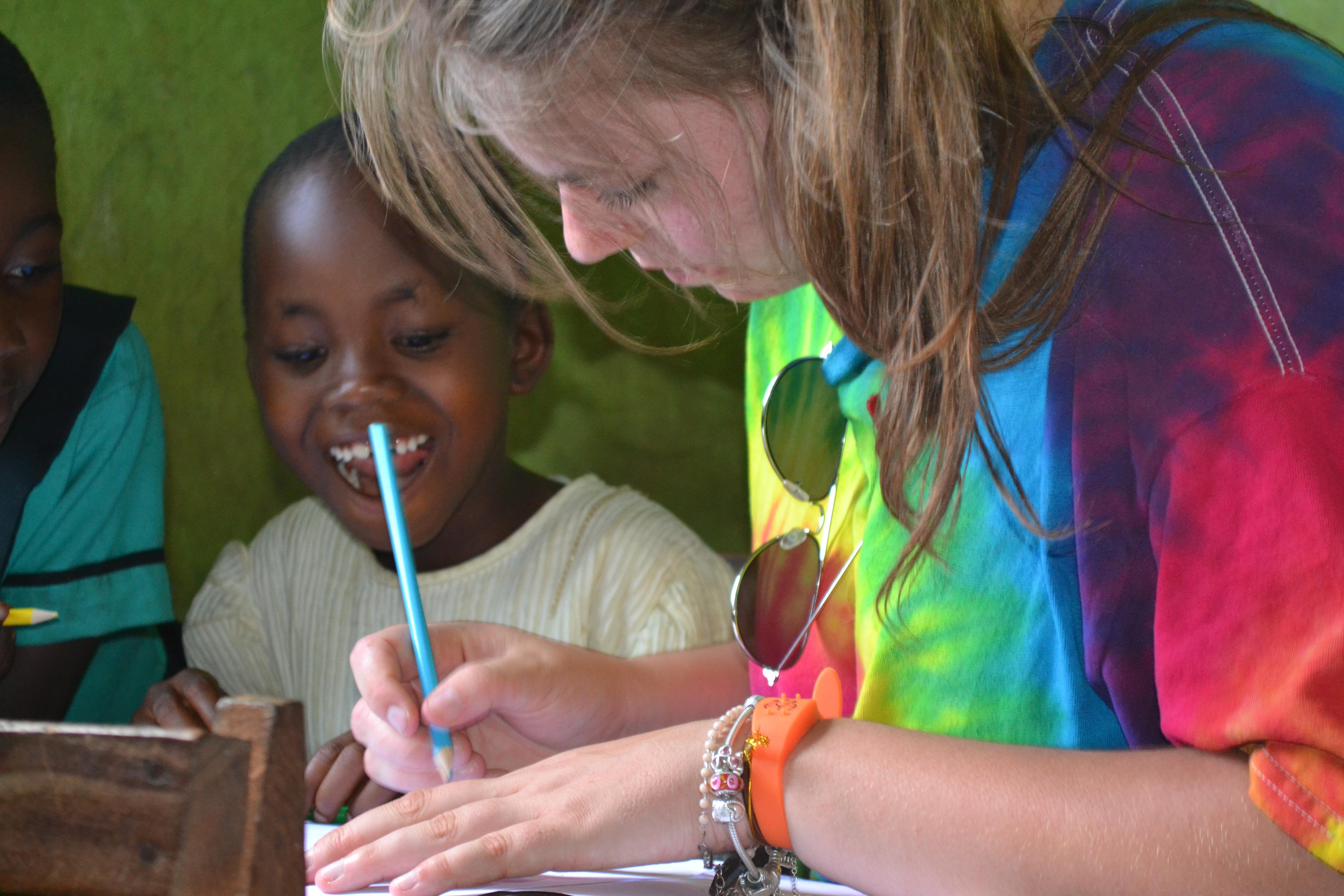 Voluntaria le explica una actividad en inglés a un estudiante como parte de su trabajo voluntario con niños en Ghana.